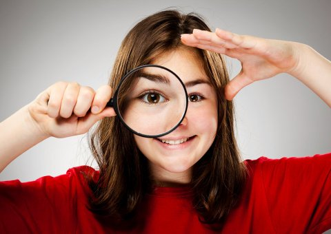 girl holding a magnifying glass